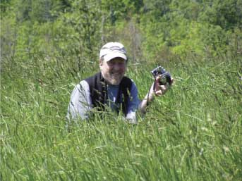 photograph of john copley, the artist, standing in a field with a camera